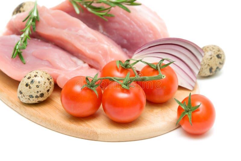 Pomodori ciliegia, carne cruda, uova, cipolle e uno sprig di rosmarino immagini stock