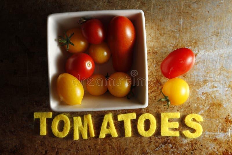 Pomodori ciliegia con i pomodori di parola immagini stock