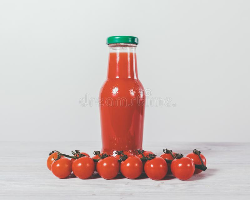 Pomodori ciliegia e succo rosso in bottiglia immagine stock libera da diritti