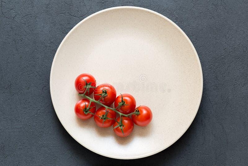 Pomodori ciliegia freschi nella ciotola sui precedenti di pietra scuri immagini stock