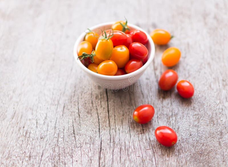 Pomodori ciliegia freschi su fondo di legno, su alimento crudo e sulla verdura fotografia stock