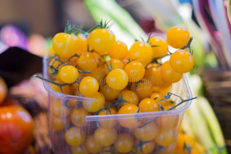 Pomodori ciliegia gialli in recipienti di plastica nel mercato fotografie stock libere da diritti
