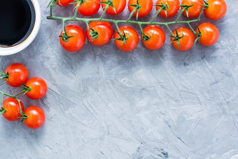 Pomodori ciliegia maturi del miele su un ramo e su una salsa balsamica in una ciotola su un fondo grigio concreto fotografia stock