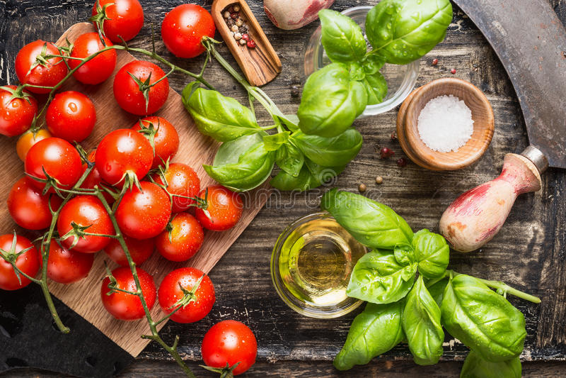 Pomodori ciliegia organici freschi con l'olio delle foglie e di olive del basilico sul tavolo da cucina rustico immagine stock libera da diritti