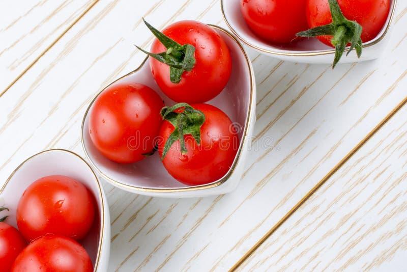 Pomodori ciliegia rossi in ciotola a forma di del cuore fotografia stock libera da diritti