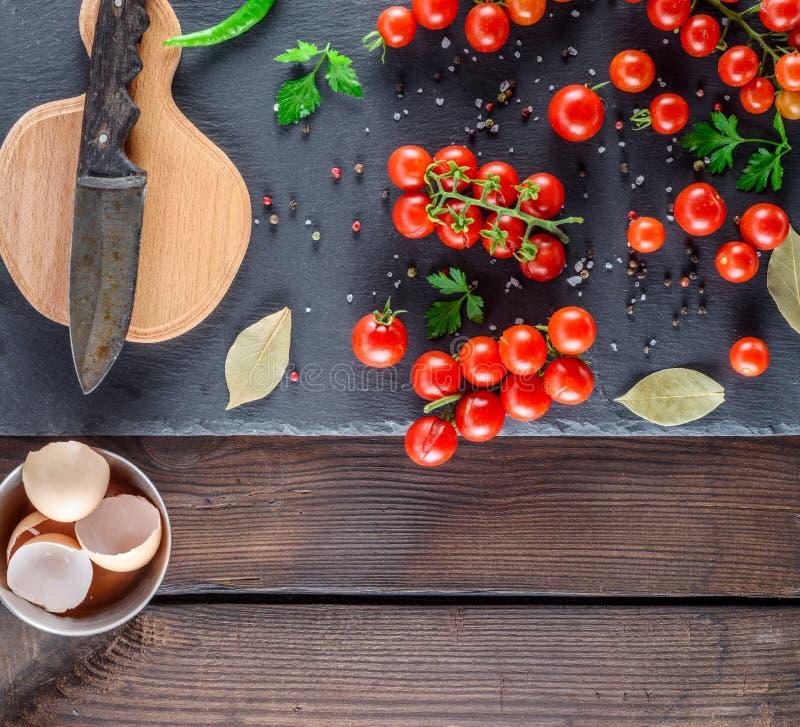 Pomodori ciliegia rossi maturi, tagliere con un vecchio coltello e le coperture delle uova del pollo fotografia stock