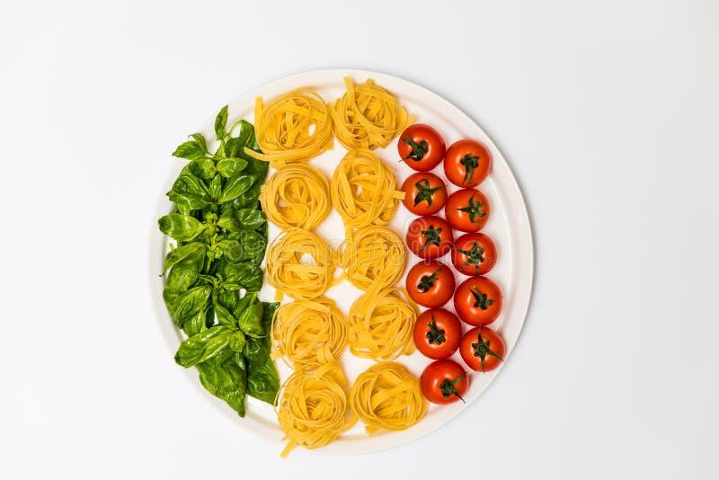 Pomodori ciliegia, spaghetti e basilico fresco su un vassoio su un fondo bianco immagine stock libera da diritti
