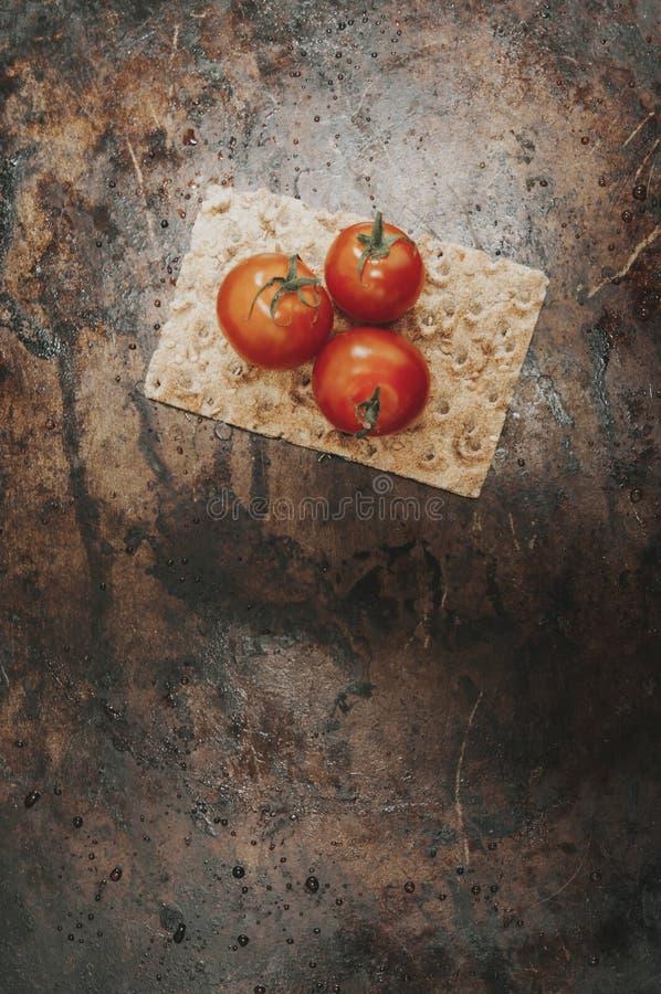 Pomodori ciliegia sul pane croccante immagini stock