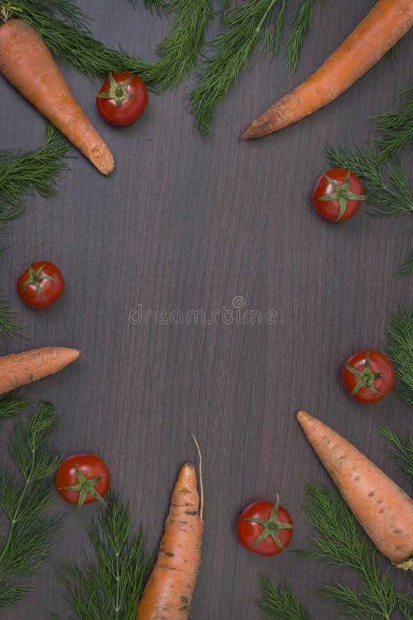 Pomodori con le carote ed il prezzemolo su un fondo di legno marrone Fondo di legno dell'alimento con i pomodori ed il prezzemolo fotografia stock libera da diritti