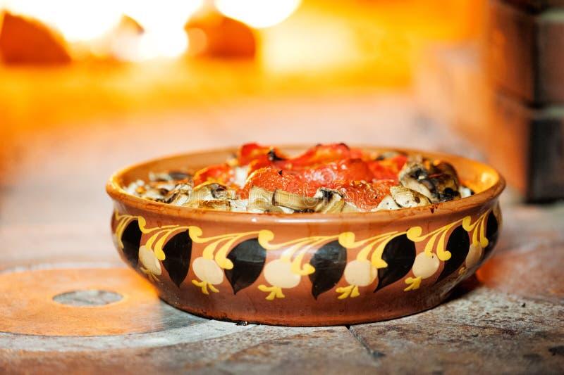 Pomodori cotti con i funghi in una ciotola dell'argilla con un ornamento sui precedenti di una stufa a legna immagini stock