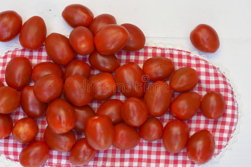 Pomodori dello spuntino della ciliegia susina su un fondo di legno bianco fotografia stock