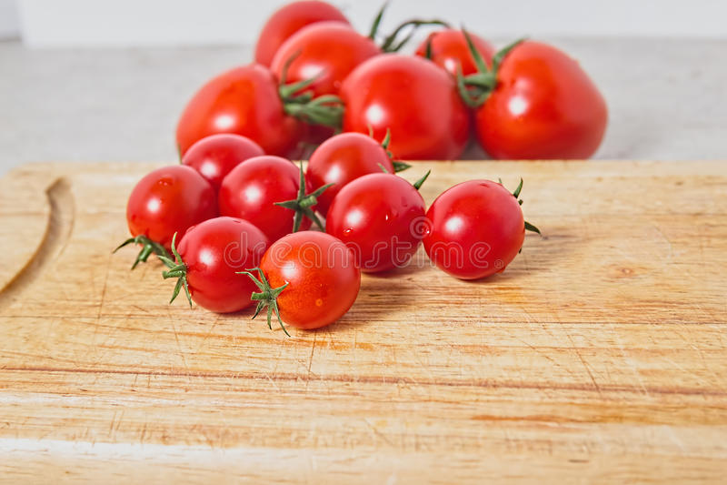 Pomodori di ciliegia su una scheda di taglio di legno Priorità bassa di verdure Bio- prodotti immagine stock libera da diritti