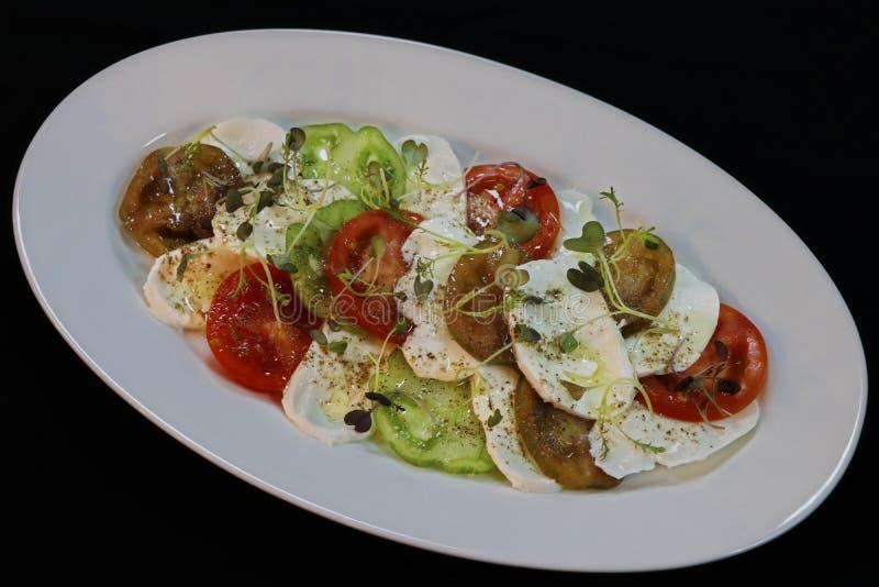 Pomodori di cimelio ed insalata della mozzarella fotografia stock