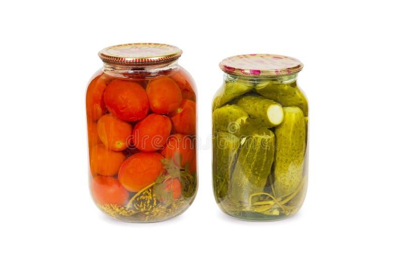 Pomodori e cetrioli conservati e marinati in un barattolo di vetro isolato fotografia stock