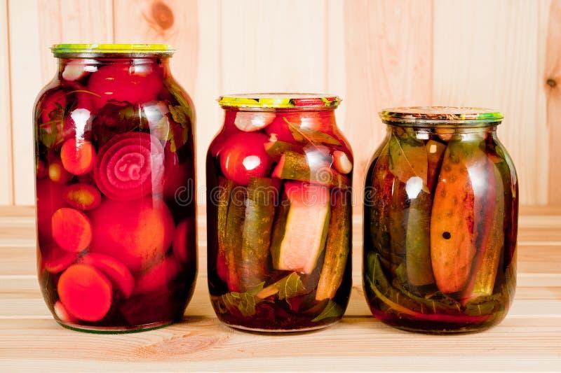 Pomodori e cetrioli inscatolati in un barattolo di vetro su un fondo di legno fotografie stock
