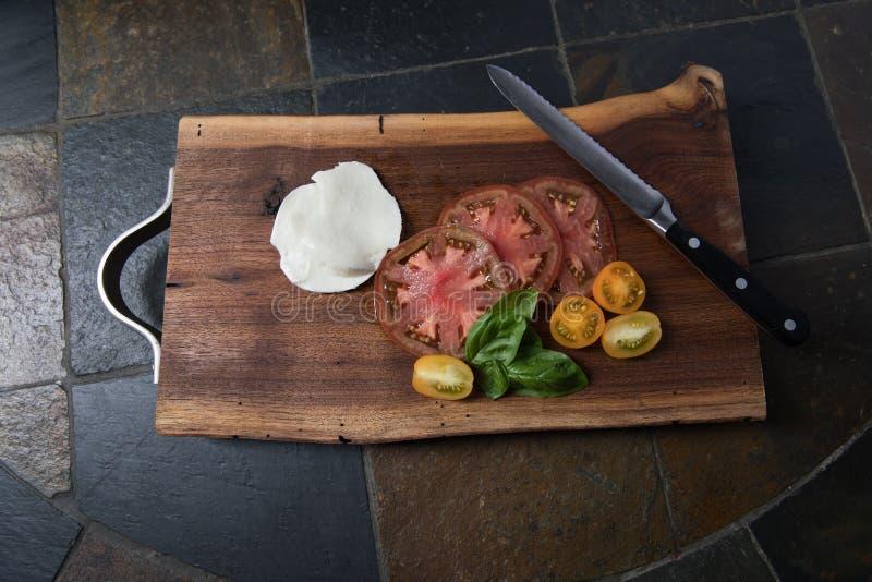 Pomodori e mozzarella affettati di cimelio sul tagliere fotografia stock libera da diritti