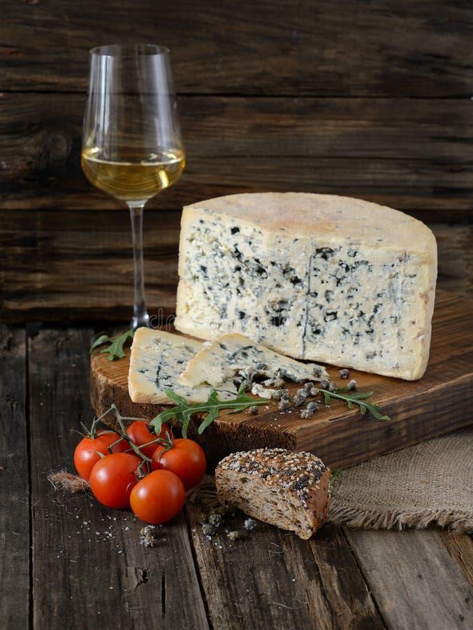 Pomodori, formaggio, capperi, pane, un bicchiere di vino su un BAC di legno fotografie stock libere da diritti