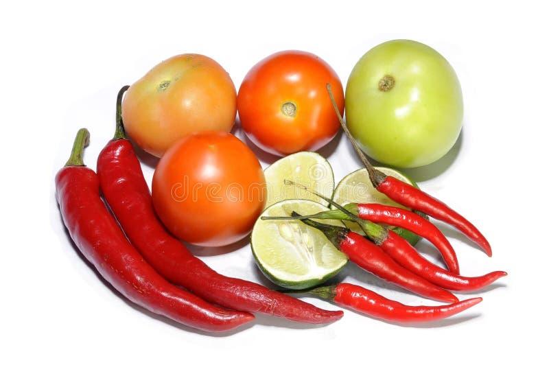 Pomodori freschi, calce tagliate e peperoncini rossi fotografia stock libera da diritti