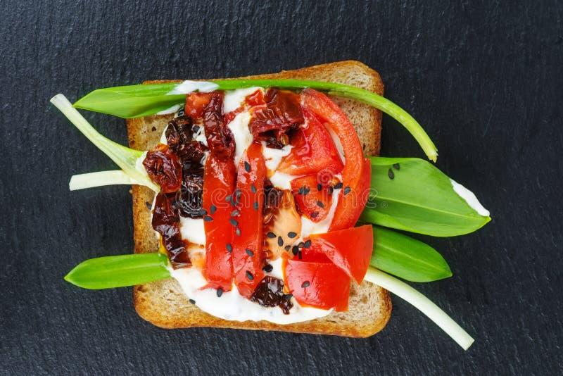 Pomodori freschi e secco verdi dei germogli di alfalfa, sulle fette tostate di pane intero isolate sulla pietra nera fotografia stock libera da diritti