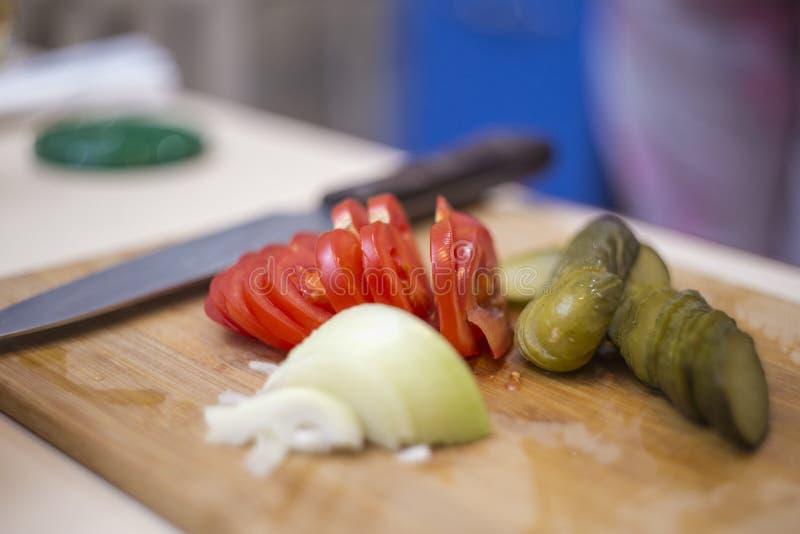 Pomodori freschi, sottaceti, cipolle su un tagliere, primo piano affettato delle verdure fotografia stock