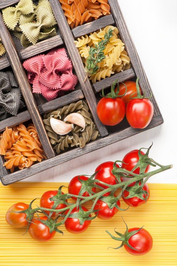 Pomodori italiani assortiti degli spaghetti e della pasta in scatola di legno fotografia stock