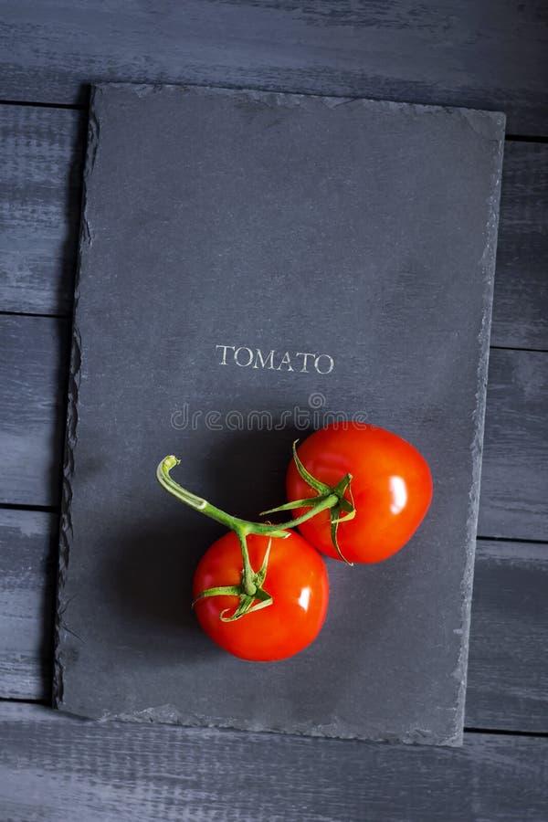 Pomodori maturi su un tagliere di pietra Copi lo spazio naturale, prodotti biologici fotografia stock libera da diritti
