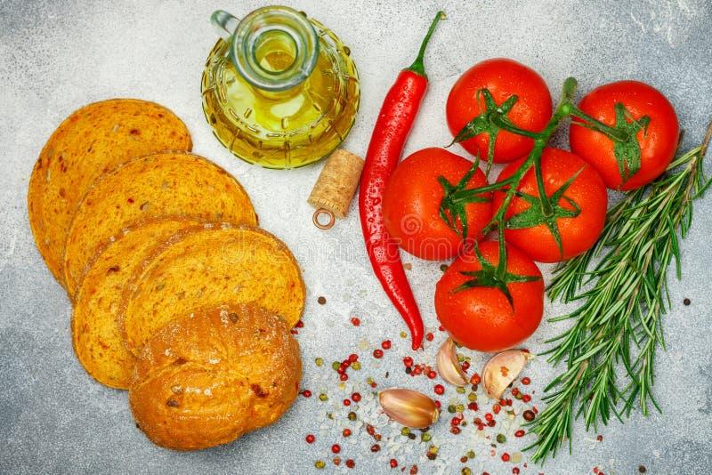 Pomodori maturi succosi freschi su un ramo, su un peperone, sui rosmarini, su un aglio e sulle spezie Pane con il pomodoro e l'ol immagini stock