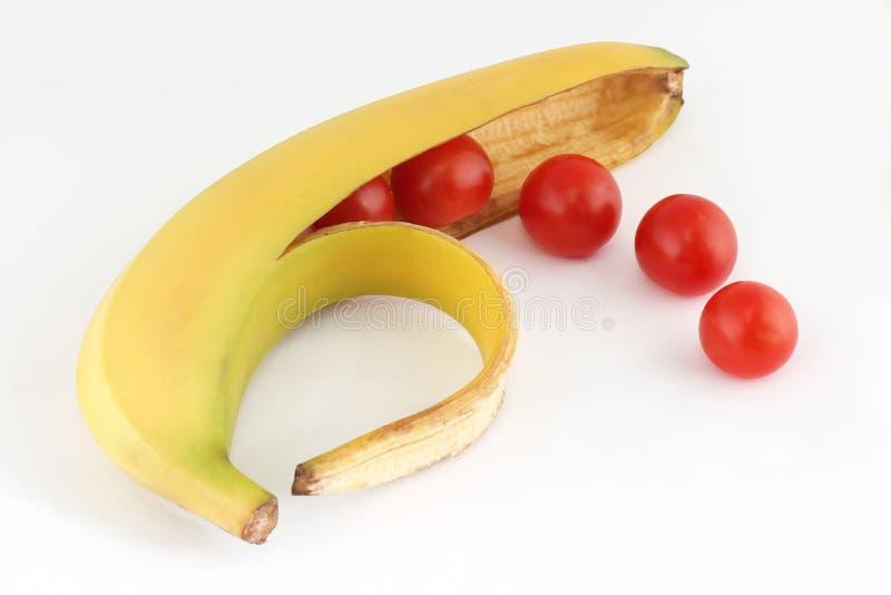 Pomodori nella banana delle coperture fotografie stock