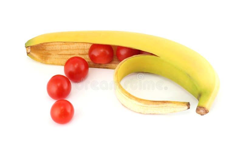 Pomodori nella banana delle coperture fotografia stock