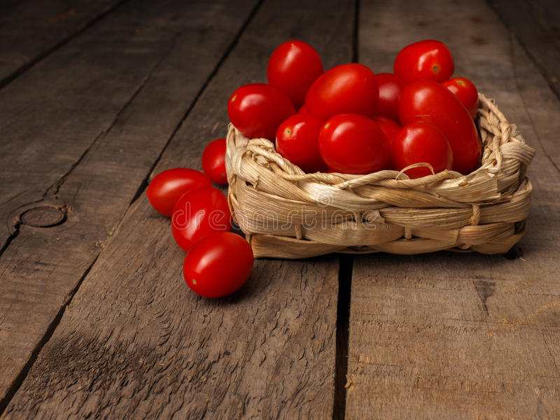 Pomodori organici dell'uva su una tavola di legno fotografia stock libera da diritti