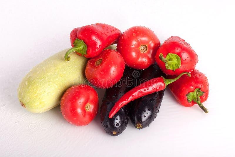 Pomodori, peperoni dolci rossi, peperoncini roventi, melanzane viola, zucchini verde nelle gocce di acqua fotografie stock libere da diritti