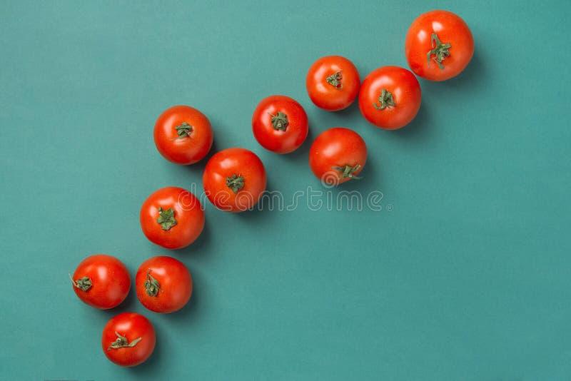 Pomodori rossi organici maturi freschi sparsi in diagonale sul fondo di verde del turchese Cucina Mediterranea greca spagnola ita immagine stock libera da diritti