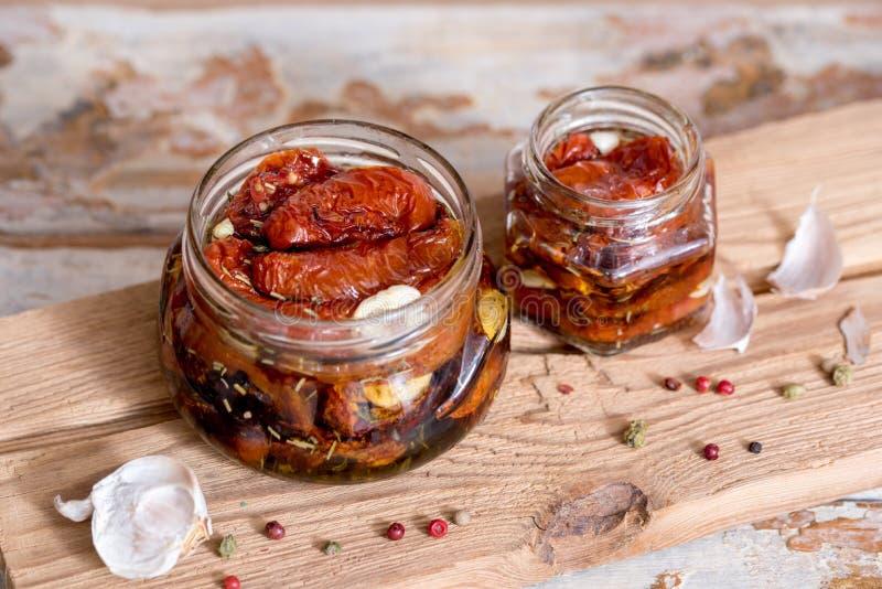 Pomodori seccati al sole con timo e sale marino in un olio d'oliva in un barattolo di vetro sui vecchi precedenti di legno Fuoco  fotografie stock