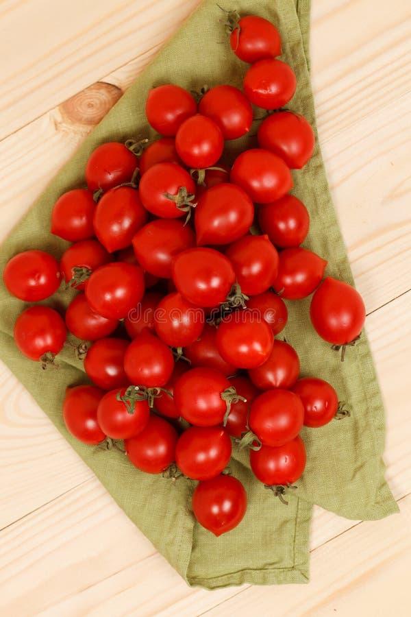 pomodori sul fondo di legno del tessuto verde immagine stock