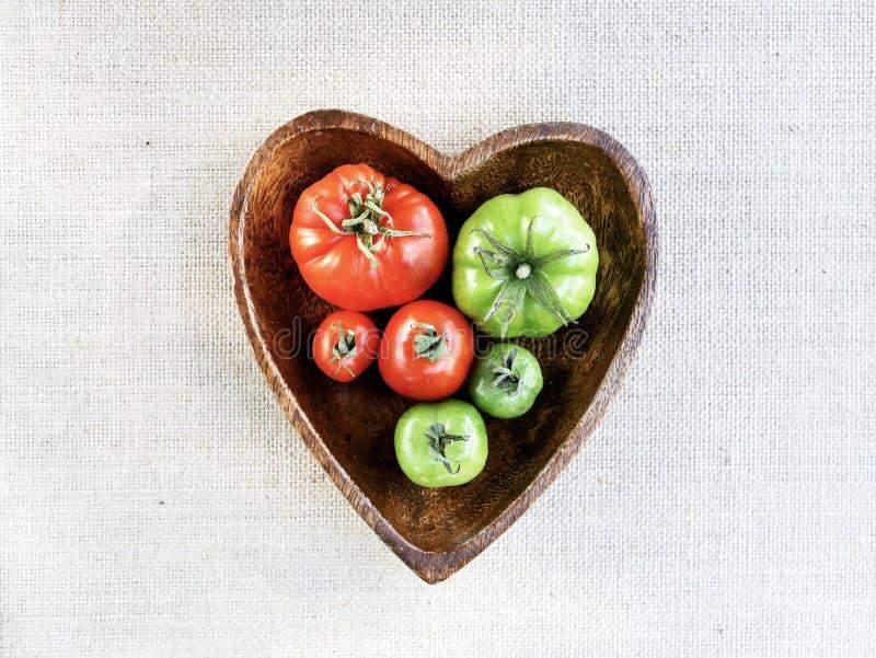 Pomodori in una ciotola a forma di del cuore fotografia stock libera da diritti