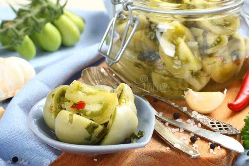 Pomodori verdi marinati in ciotola blu ed in barattolo di vetro immagini stock libere da diritti