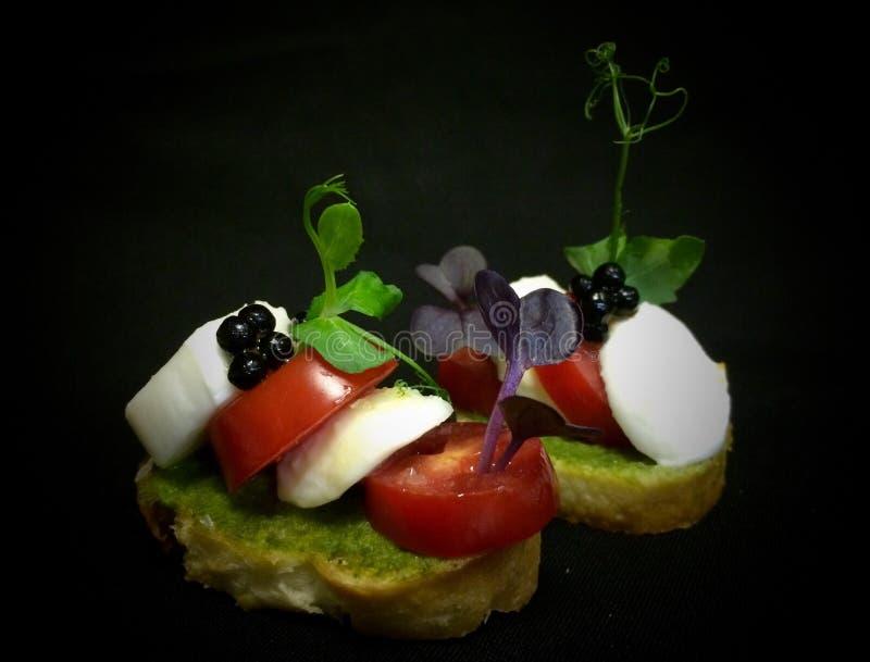 Pomodoro ciliegia e mozzarella su un pane croccante fotografia stock libera da diritti