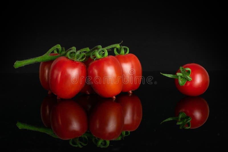 Pomodoro ciliegia rosso isolato su vetro nero immagini stock