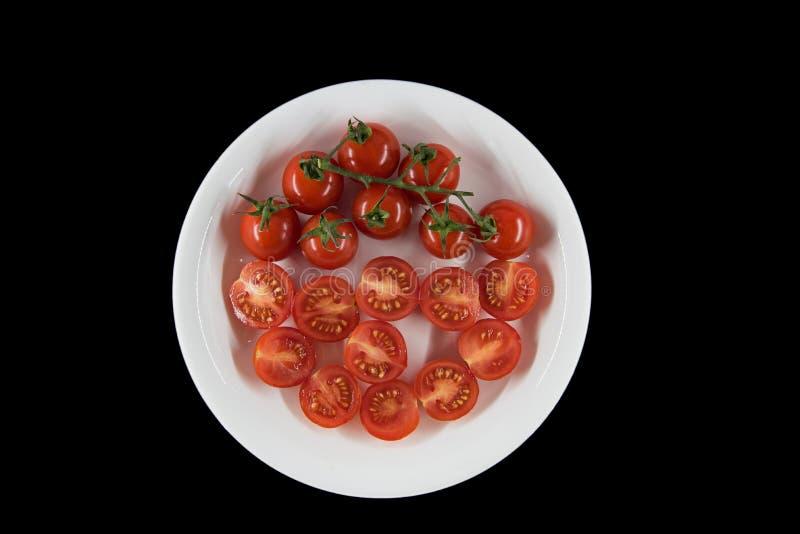 pomodoro cuted sul piatto con fondo nero, vista superiore immagine stock libera da diritti