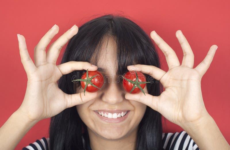 Pomodoro della holding della donna sopra gli occhi immagini stock