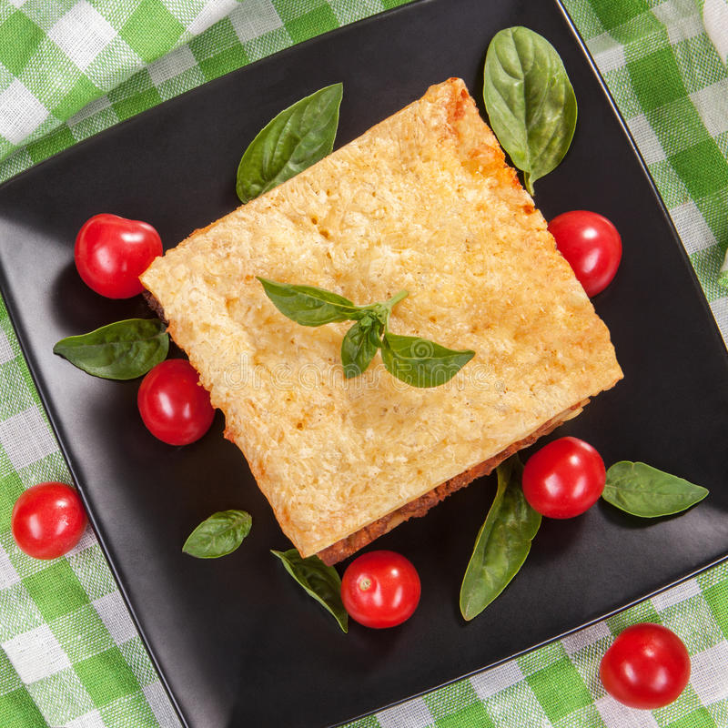 Pomodoro e basilico saporiti delle lasagne al forno su un piatto del quadrato nero immagine stock