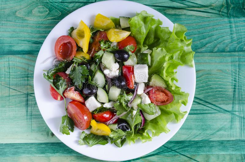 Pomodoro ed olive di verdure del capsico del cetriolo dell'insalata su uno sfondo naturale del piatto bianco con lo spazio della  immagine stock libera da diritti