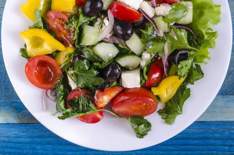 Pomodoro ed olive di verdure del capsico del cetriolo dell'insalata su uno sfondo naturale del piatto bianco con lo spazio della  immagini stock