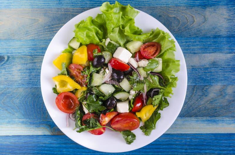 Pomodoro ed olive di verdure del capsico del cetriolo dell'insalata su uno sfondo naturale del piatto bianco con lo spazio della  immagine stock