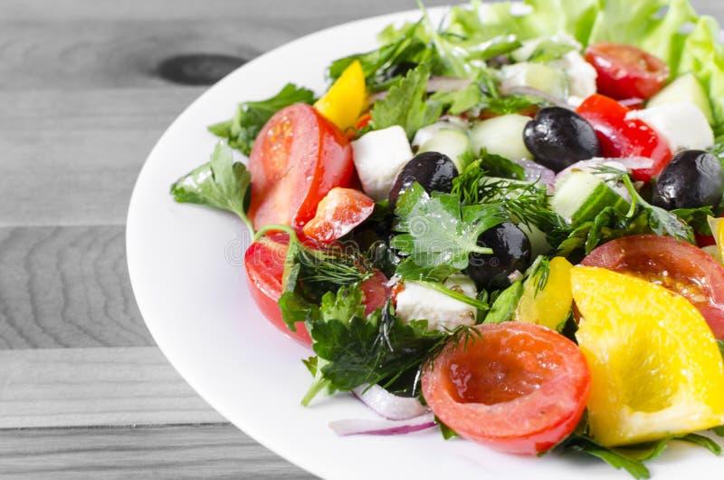 Pomodoro ed olive di verdure del capsico del cetriolo dell'insalata su uno sfondo naturale del piatto bianco con lo spazio della  fotografie stock libere da diritti