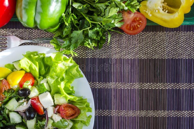 Pomodoro ed olive di verdure del capsico del cetriolo dell'insalata su uno sfondo naturale del piatto bianco con lo spazio della  fotografia stock