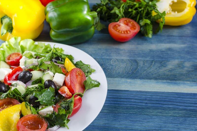 Pomodoro ed olive di verdure del capsico del cetriolo dell'insalata su uno sfondo naturale del piatto bianco con lo spazio della  fotografie stock