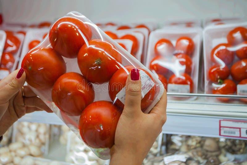 Pomodoro imballato con la mano della donna nel supermercato immagine stock libera da diritti
