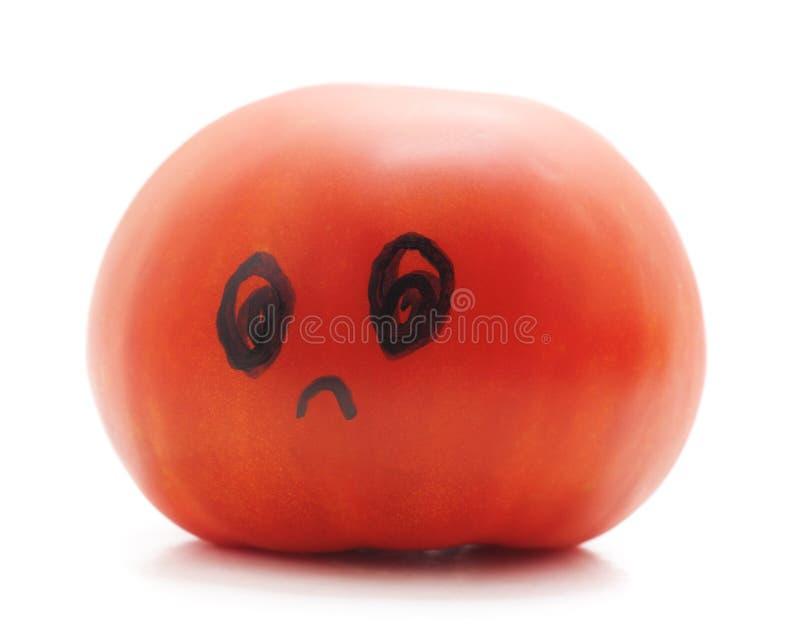 Pomodoro maturo con un viso umano fotografie stock libere da diritti