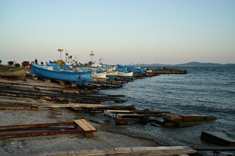 Fishermen`s boats stand on the shore of the seaport of the seaside resort town of Pomorie. POMORIE, BULGARIA - JUNE 30, 2019: Fishermen`s boats stand on the stock images